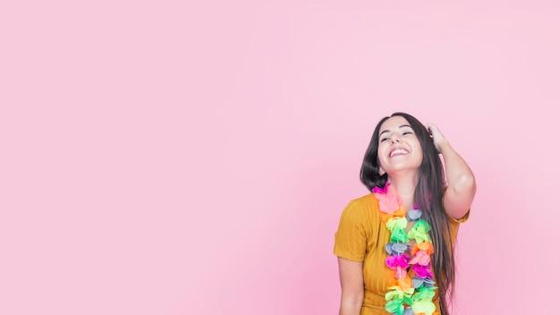 Jovem mulher de sorriso com a festão falsificada colorida que está contra o fundo cor-de-rosa