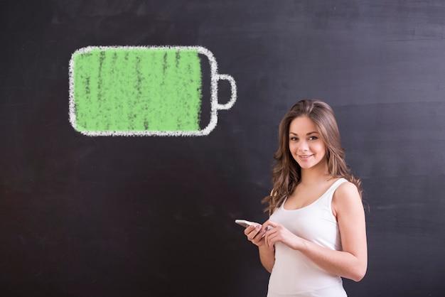 Jovem mulher de sorriso com smartphone e bateria completa.