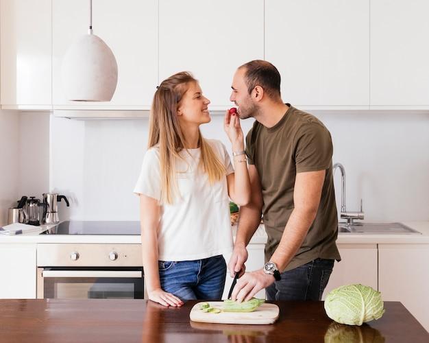 Jovem mulher de sorriso que alimenta a salada a seu marido na cozinha