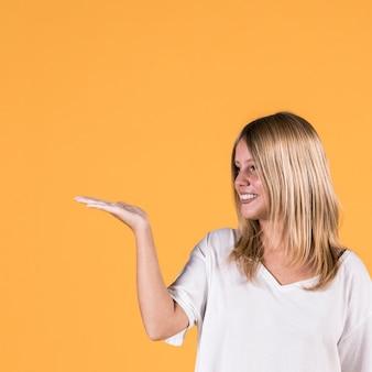 Jovem mulher de sorriso que apresenta o sinal do gesto no fundo colorido