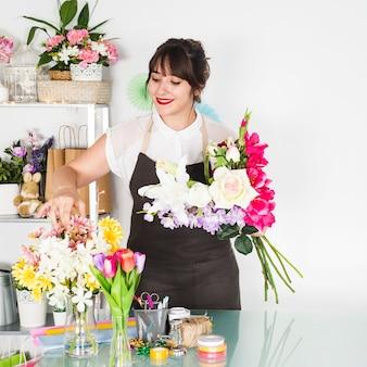 Jovem mulher de sorriso que classifica flores na loja floral