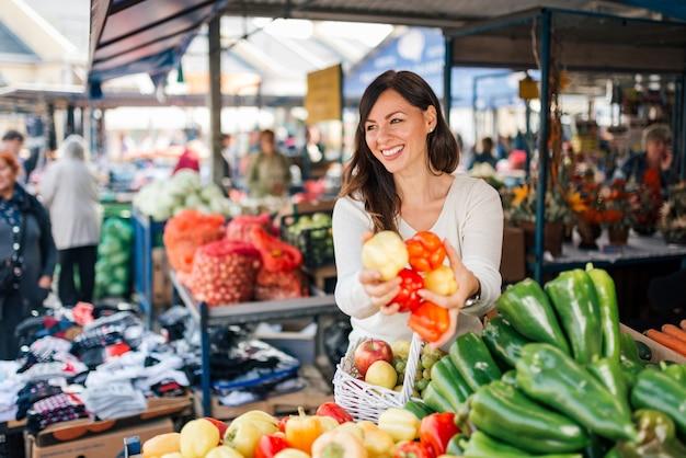 Jovem mulher de sorriso que compra legumes frescos.