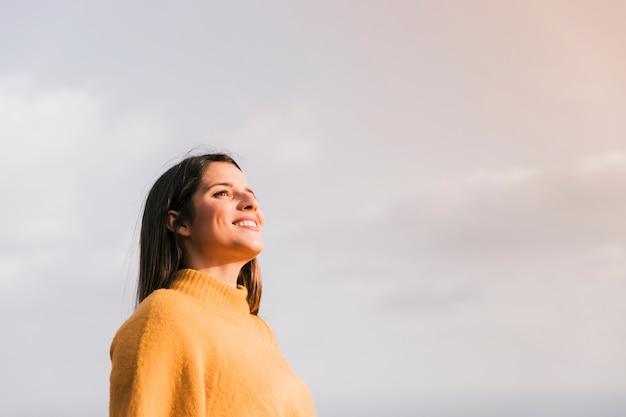 Jovem mulher de sorriso que está contra o céu que olha afastado