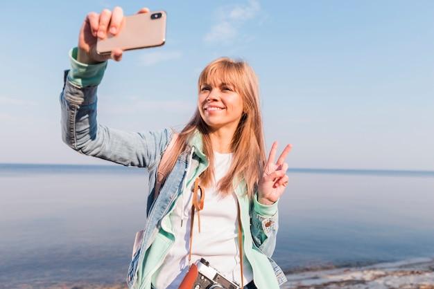 Jovem mulher de sorriso que está na frente do mar que toma o selfie no smartphone