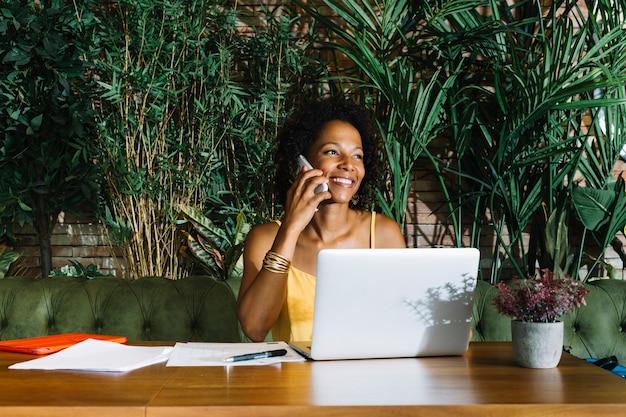 Jovem mulher de sorriso que fala no telefone móvel com portátil; documentos e caneta na mesa de madeira
