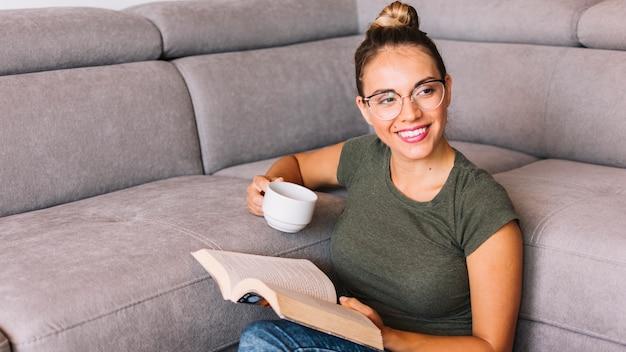 Jovem mulher de sorriso que guarda a xícara de café e os livros que olham afastado