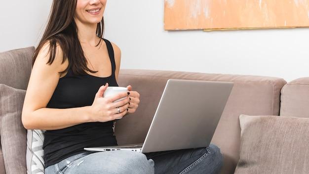 Jovem mulher de sorriso que guarda o copo de café à disposição usando o portátil
