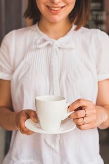 Jovem mulher de sorriso que guarda o copo do café saboroso