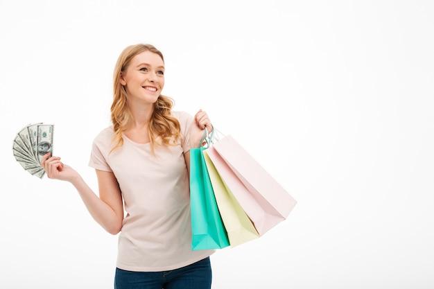 Jovem mulher de sorriso que guarda o dinheiro e os sacos de compras.