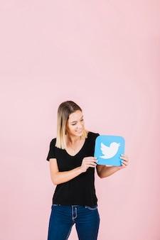 Jovem mulher de sorriso que guarda o ícone do twitter no fundo cor-de-rosa