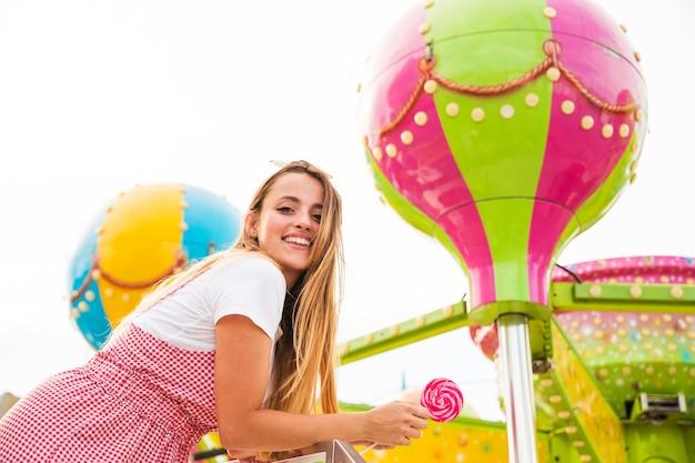 Jovem mulher de sorriso que guarda o pirulito no parque de diversões