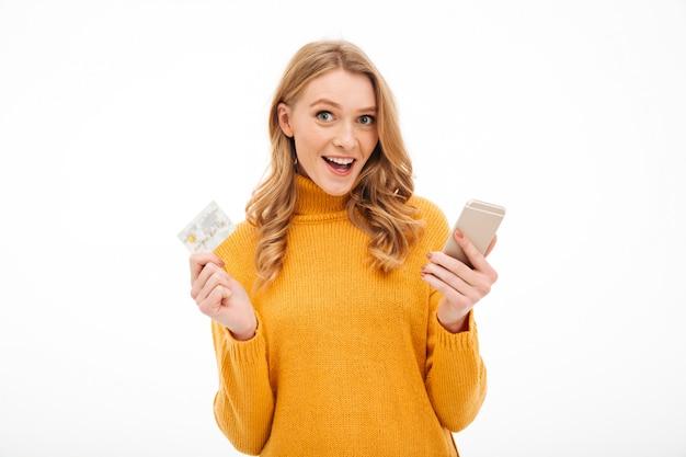 Jovem mulher de sorriso que guarda o telefone móvel e o cartão de crédito.