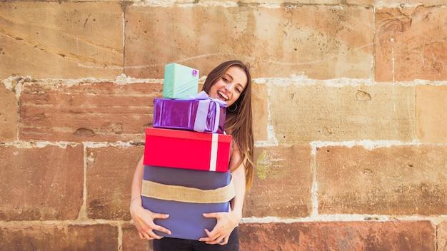 Jovem mulher de sorriso que guarda presentes empilhados contra a parede resistida