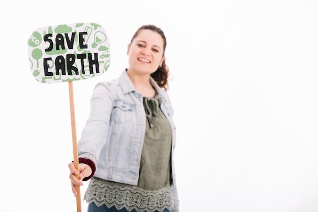 Jovem mulher de sorriso que guarda salvar o cartaz da terra contra o fundo branco