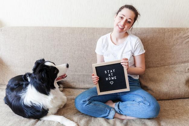Jovem mulher de sorriso que joga com filhote de cachorro bonito border collie no sofá em casa dentro de casa