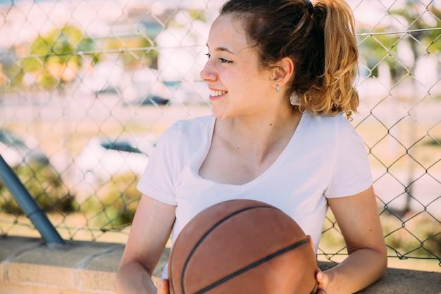 Jovem mulher de sorriso que mantém o basquetebol contra o elo de corrente no campo de jogos