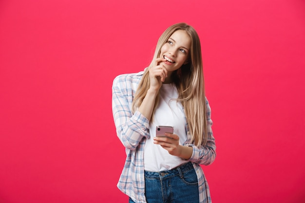 Jovem mulher de sorriso que pensa ao usar o smartphone.