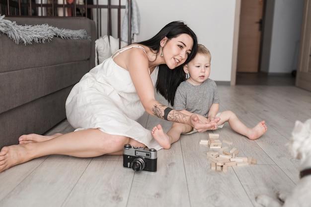 Jovem mulher de sorriso que senta-se com o filho pequeno que chama seu cão em casa