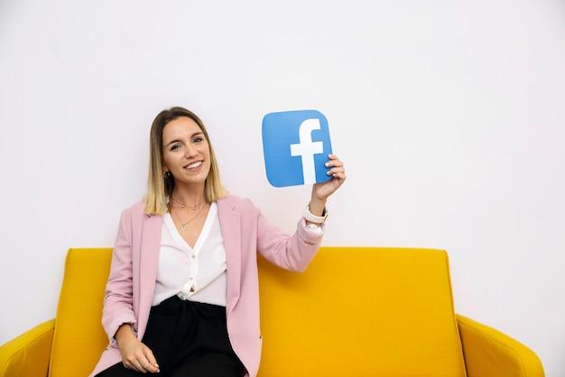 Jovem mulher de sorriso que senta-se no sofá amarelo que guarda o ícone do facebook
