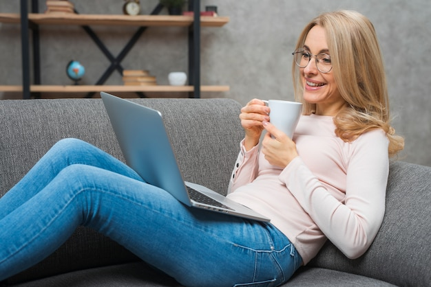 Jovem mulher de sorriso que senta-se no sofá que guarda a xícara de café que olha o portátil