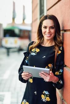 Jovem mulher de sorriso que usa a tabuleta digital ao ar livre.