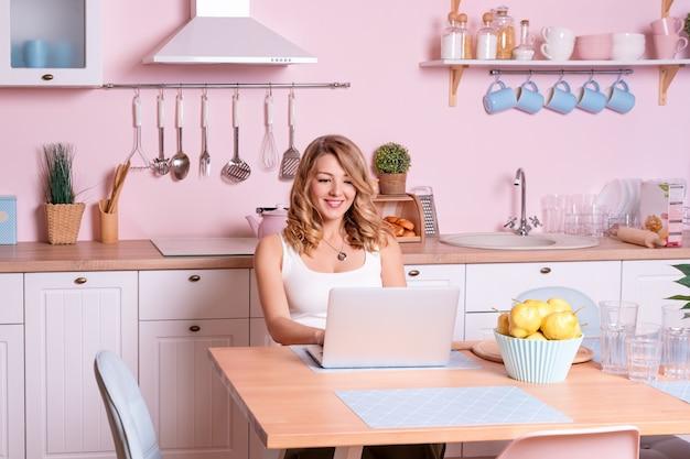 Jovem mulher de sorriso que usa o portátil na cozinha em casa. mulher loira trabalha no computador, freelancer ou blogueiro trabalhando em casa