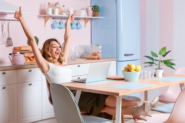 Jovem mulher de sorriso que usa o portátil na cozinha em casa.