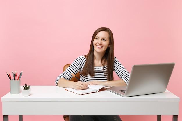 Jovem mulher de sucesso olhando para o lado escrevendo notas na cadeira do caderno, trabalhando na mesa branca com o laptop pc contemporâneo