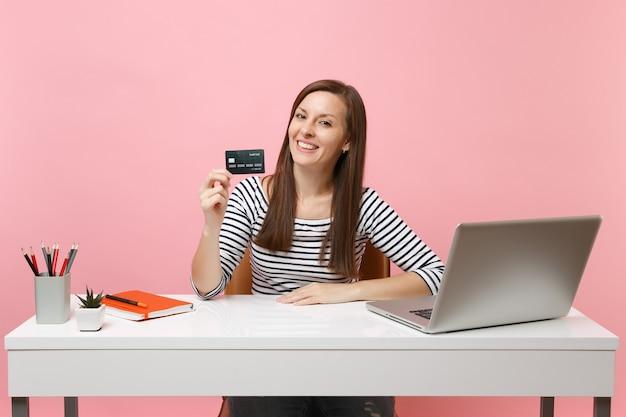 Jovem mulher de sucesso segurando um cartão de crédito, sentado em uma mesa branca, com um laptop pc contemporâneo