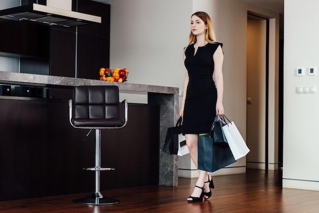 Jovem mulher de sucesso voltando para casa depois de fazer compras com sacolas.