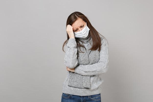 Jovem mulher de suéter cinza, lenço com máscara facial estéril colocar a mão na cabeça isolada em um fundo cinza em estúdio. tratamento de doença doente doente de estilo de vida saudável, conceito de estação fria. simule o espaço da cópia.