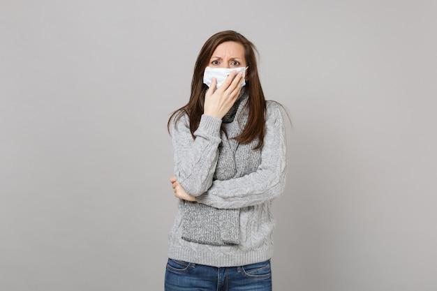 Jovem mulher de suéter cinza, lenço com máscara facial estéril colocou a mão na boca isolada em um fundo cinza em estúdio. estilo de vida saudável doente doente doença tratamento conceito de estação fria. simule o espaço da cópia.