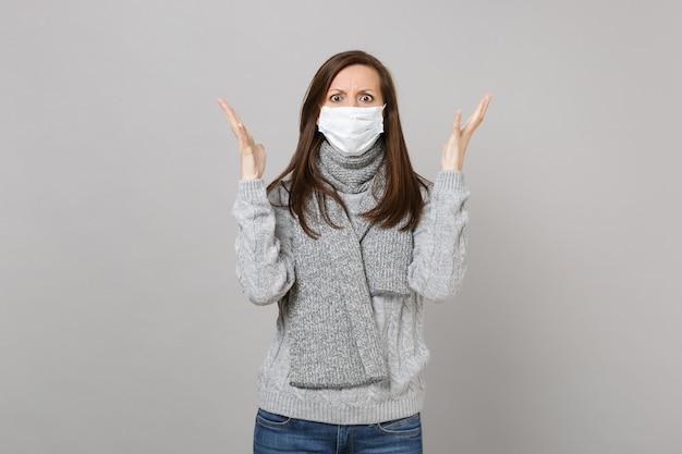 Jovem mulher de suéter cinza, lenço com máscara facial estéril, espalhando as mãos isoladas em um fundo cinza em estúdio. tratamento de doença doente doente de estilo de vida saudável, conceito de estação fria. simule o espaço da cópia.