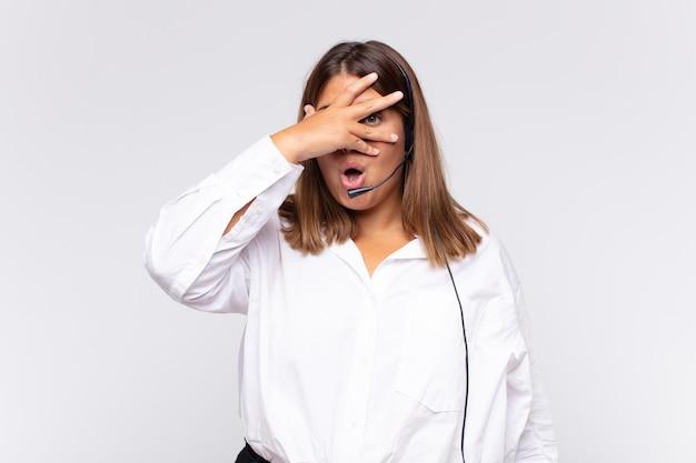 Jovem mulher de telemarketing parecendo chocada, assustada ou apavorada, cobrindo o rosto com a mão e espiando entre os dedos