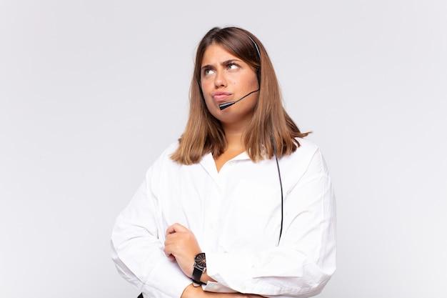 Jovem mulher de telemarketing pensando, sentindo-se em dúvida e confusa, com diferentes opções, imaginando qual decisão tomar