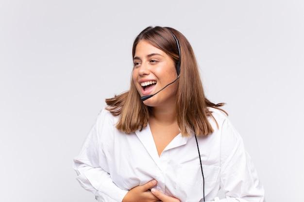 Jovem mulher de telemarketing rindo alto de uma piada hilária, sentindo-se feliz e alegre, se divertindo