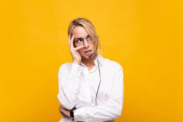 Jovem mulher de telemarketing se sentindo entediada, frustrada e com sono depois de uma tarefa cansativa, enfadonha e tediosa, segurando o rosto com a mão