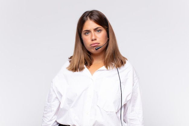 Jovem mulher de telemarketing se sentindo triste e chorona com uma expressão infeliz, chorando com uma atitude negativa e frustrada