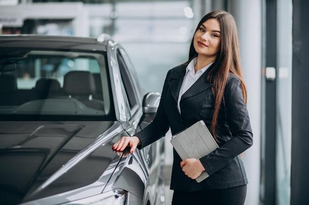 Jovem mulher de vendas no salão do carro em pé ao lado do carro