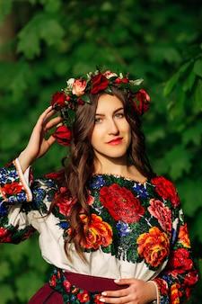 Jovem mulher de vestido bordado com miçangas coloridas com coroa de flores