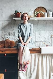 Jovem mulher de vestido cinza puxa maçãs fora do saco de pano de malha comprador de saco de cordas na cozinha