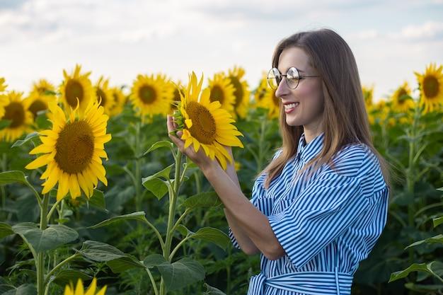 Jovem mulher de vestido e óculos, apreciando as flores em um campo de girassol.
