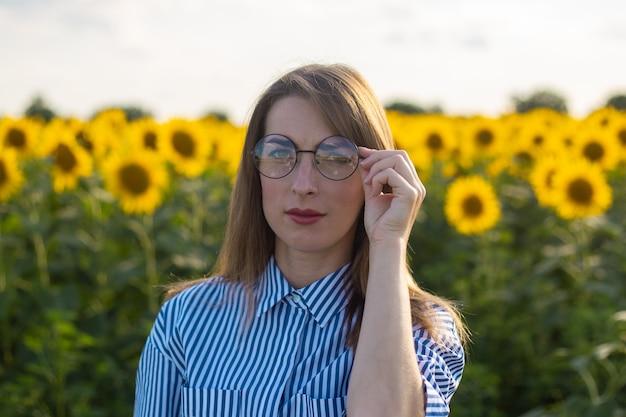 Jovem mulher de vestido e óculos em um campo de girassol.