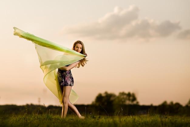 Jovem mulher de vestido fazendo pose de ginástica e segurando o pano amarelo num dia de verão com paisagem de campo no fundo