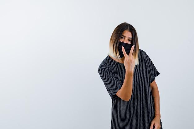 Jovem mulher de vestido preto, máscara preta, mostrando um gesto de paz e parecendo confiante, vista frontal.