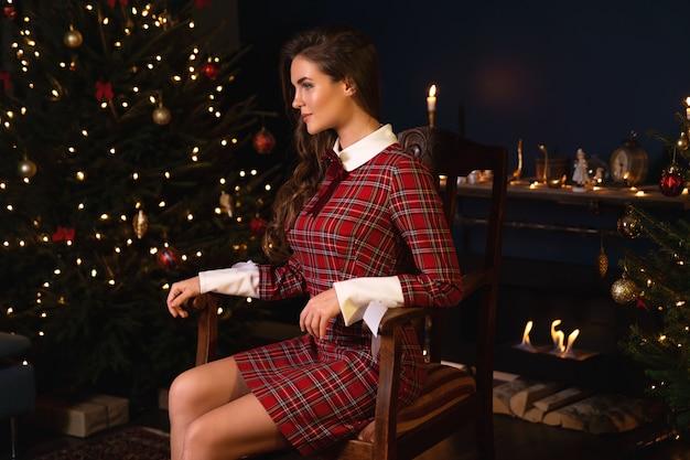 Jovem mulher de vestido quente xadrez está sentado ao lado de uma lareira