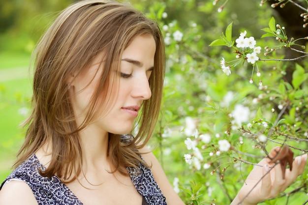 Jovem mulher de vestido relaxante no jardim