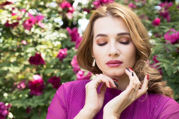 Jovem mulher de vestido roxo, posando em um jardim de peônias