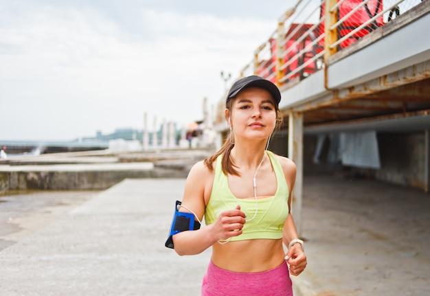 Jovem mulher decidida corre ao ar livre e ouve música. corrida matinal