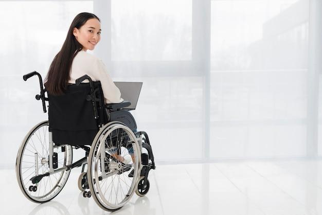 Jovem mulher deficiente que usa o portátil que olha sobre o ombro